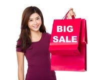 La mujer feliz de las compras aumenta para arriba los bolsos que muestran venta grande Fotos de archivo libres de regalías