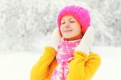 La mujer feliz del retrato del invierno de la moda que lleva la bufanda hecha punto colorida del suéter del sombrero goza sobre n Fotografía de archivo