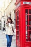 La mujer feliz del viajero de la ciudad se coloca al lado de una cabina de teléfono roja n Londres fotografía de archivo libre de regalías