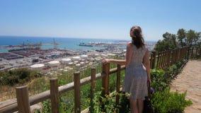 La mujer feliz en la colina de Montjuic disfruta de panorama del mar y del puerto de Barcelona almacen de video
