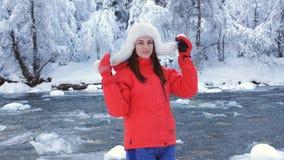 La mujer feliz en invierno ajardina cerca de un río de la montaña y disfruta del aire libre y es feliz almacen de metraje de vídeo