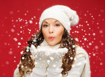 La mujer feliz en invierno viste soplar en las palmas Imagen de archivo