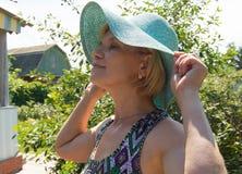 La mujer feliz en sombrero y el verano visten la presentación en un fondo de árboles verdes en su jardín Fotografía de archivo libre de regalías