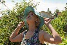 La mujer feliz en sombrero y el verano visten la presentación en un fondo de árboles verdes en su jardín Fotografía de archivo