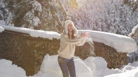 La mujer feliz en su?ter del punto y sombrero de piel disfruta de una ma?ana escarchada soleada, lanza la nieve y est? haciendo g metrajes