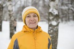 La mujer feliz en un casquillo amarillo brillante y un jacke Imagenes de archivo