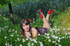 La mujer feliz en un jardín de la primavera está en color, con los zapatos rojos Fotografía de archivo