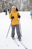 La mujer feliz en una chaqueta amarilla brillante en los esquís foto de archivo