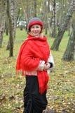 La mujer feliz en una estola del rojo y un sombrero cuesta entre abedules en la madera Fotografía de archivo libre de regalías