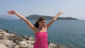 La mujer feliz en vestido rosado aumenta sus brazos encima y al lado, cámara lenta, 4K almacen de metraje de vídeo
