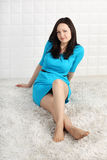 La mujer feliz en vestido se sienta en la alfombra suave Imagen de archivo libre de regalías