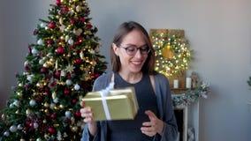 La mujer feliz en vidrios, recibe el regalo de la Navidad en el fondo del árbol de navidad en hogar adornado Feliz Año Nuevo almacen de video