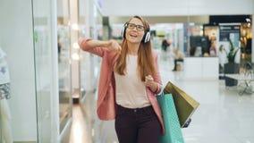 La mujer feliz está disfrutando de música en auriculares, está bailando y está cantando en el pasillo del centro comercial que so metrajes