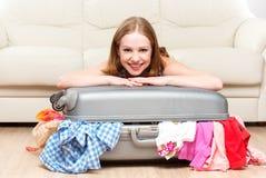 La mujer feliz está embalando la maleta en casa Imagen de archivo