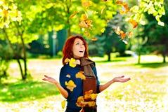 La mujer feliz está lanzando las hojas de otoño Fotografía de archivo libre de regalías