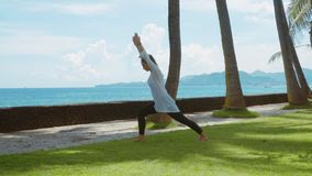La mujer feliz está practicando la yoga, actitud del guerrero, ejercicio de la balanza, estirando, en la playa, el fondo hermoso,