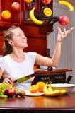 La mujer feliz está cocinando la ensalada de fruta Fotos de archivo
