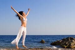 La mujer feliz está saltando en la playa Fotografía de archivo