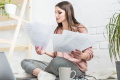 La mujer feliz examina el papel que se sienta cerca del ordenador port?til, la muchacha que el freelancer trabaja con los documen fotografía de archivo