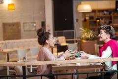 La mujer feliz felicita a su novia con la actual caja mientras que se sienta en el café imagen de archivo libre de regalías