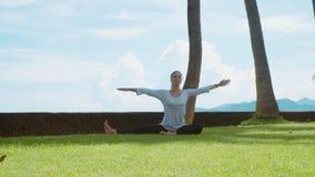 La mujer feliz hace la práctica de la yoga, estiramiento encima y a la pierna, reflexionando sobre la playa, el fondo hermoso y l