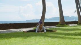 La mujer feliz hace práctica y estiramiento de la yoga abajo adelante en guita cruzada en la playa del océano, el fondo hermoso y