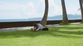 La mujer feliz hace práctica y estiramiento de la yoga abajo a la pierna en la playa del océano, el fondo hermoso y los sonidos d