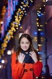 La mujer feliz hermosa en capa anaranjada camina en ciudad de la noche Imagen de archivo