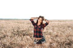 La mujer feliz hermosa en el campo, tarde soleada, pone en cortocircuito la camisa Pelo hermoso, piel bronceada, concepto de disf Fotografía de archivo