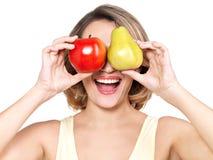 La mujer feliz hermosa joven sostiene la manzana y la pera. Imagen de archivo