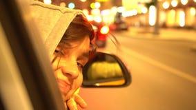 La mujer feliz inclina hacia fuera la ventanilla del coche lateral del pasajero metrajes