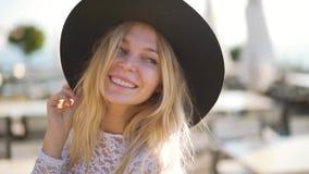 La mujer feliz joven atractiva que camina en café, aumenta con éxito sus brazos para arriba Mire la cámara almacen de metraje de vídeo