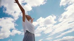 La mujer feliz joven aumenta las manos en el fondo de las nubes blancas y del cielo azul brillante almacen de video