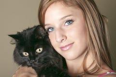 La mujer feliz joven con es gato negro Fotografía de archivo