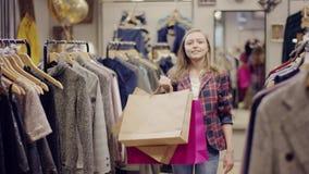 La mujer feliz joven con los bolsos de compras camina al estante de la ropa en una tienda y buscar de la ropa el nuevo vestido almacen de video
