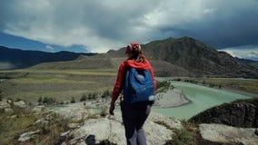 La mujer feliz joven del torist con la mochila y el casquillo alcanza al borde de la montaña y pone sus manos en el aire back metrajes