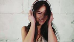 La mujer feliz joven es música que escucha en auriculares, cabeza que agita y el baile almacen de video