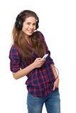 La mujer feliz joven escucha la música aislada en blanco imagenes de archivo