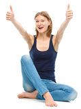 La mujer feliz joven está mostrando el pulgar encima de la muestra Fotografía de archivo libre de regalías