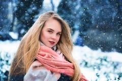 La mujer feliz joven goza de nieve en el parque de la ciudad del invierno al aire libre Fotografía de archivo libre de regalías