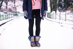 La mujer feliz joven goza de nieve en el parque de la ciudad del invierno al aire libre Foto de archivo
