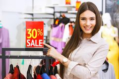 La mujer feliz joven hermosa con venta roja firma adentro un sto de la ropa Fotografía de archivo