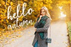 La mujer feliz joven hermosa en ropa estacional caliente elegante con un bolso de cuero se está colocando en el camino en el parq foto de archivo libre de regalías