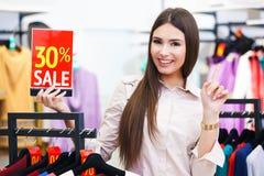 La mujer feliz joven hermosa holiding venta roja firma adentro una ropa Imagen de archivo