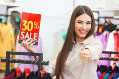 La mujer feliz joven hermosa holiding venta roja firma adentro una ropa Imagen de archivo libre de regalías