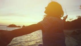 La mujer feliz joven lleva a cabo la mano de su amigo y tienta el suyo a los paseos a lo largo de la playa durante puesta del sol almacen de metraje de vídeo