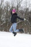 La mujer feliz joven que el brunette salta en nieve imágenes de archivo libres de regalías