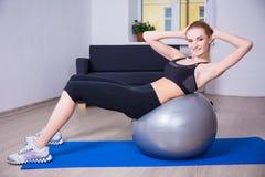 La mujer feliz joven que hace aptitud ejercita con la bola de los pilates en h Imagen de archivo