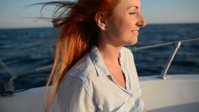 La mujer feliz joven que se sienta en cortador que va mira el mar adriático almacen de video