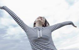 La mujer feliz joven se está abriendo los brazos en el cielo azul fotografía de archivo libre de regalías